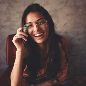 Girl Smiling While Holding Her Glasses